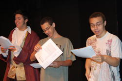 Three people on stage conducting a Reader's Theater session